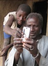 Alaburu Maiga, right, tries to use the camera on his cellphone with the help of an unidentified boy in the village of Gono, Mali, last year.