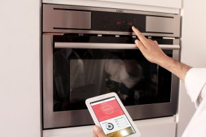A person turn off the electric oven while holding a tablet with the CITYOPT app.
